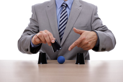 Cup and ball guessing game success with businessman hand revealing the correct cup